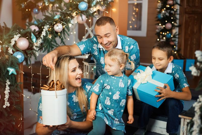 Smiling mother and father hands christmas gifts to their two children stock photos