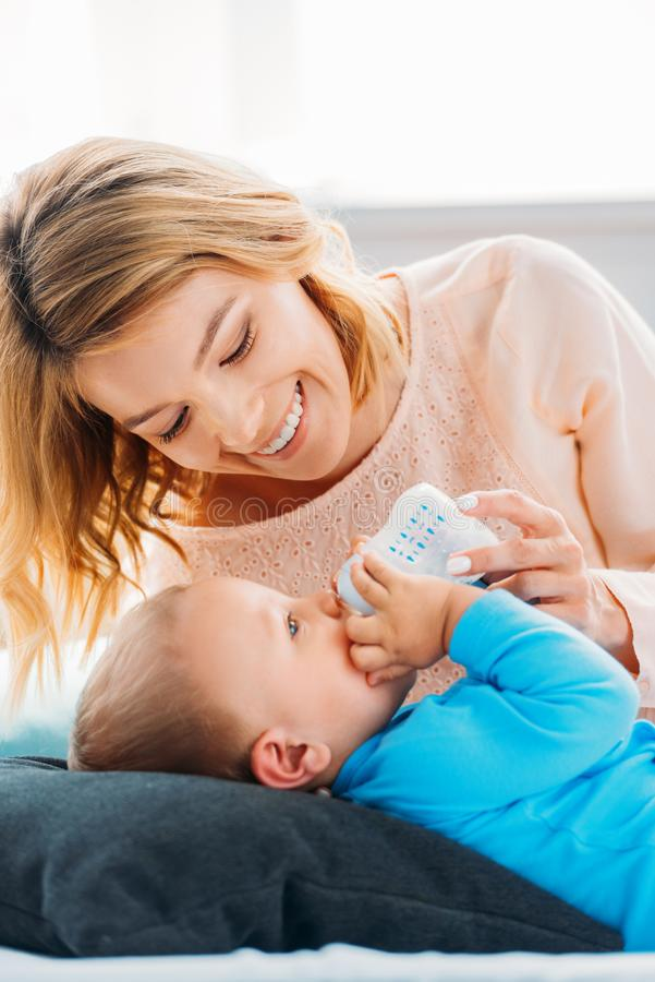 Smiling mother feeding her little child. With baby bottle on bed at home royalty free stock photo
