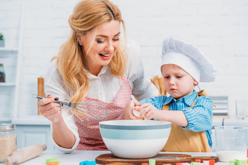 Smiling mother with hand beater and little boy royalty free stock photography