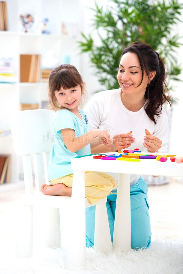 Free Smiling Mother Helps A Little Daughter To Sculpt Figurines From Plasticine. Children`s Creativity. Happy Family Stock Photography - 144035012