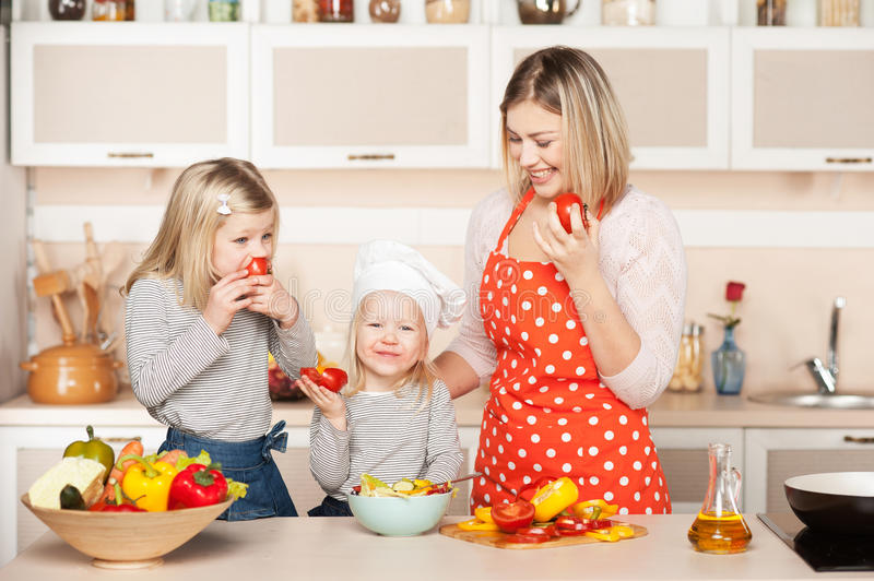 Smiling mother and her daughters eating tomatos stock image