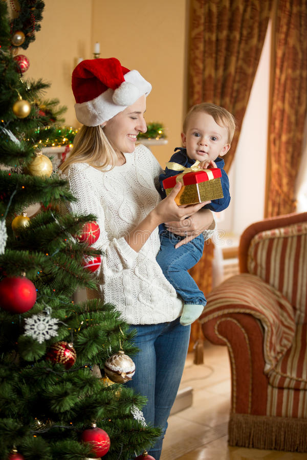 Smiling mother holding her baby boy at Christmas tree and giving stock image