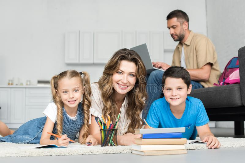 Smiling mother and kids looking at camera while doing homework together and man. Using laptop on sofa at home royalty free stock images