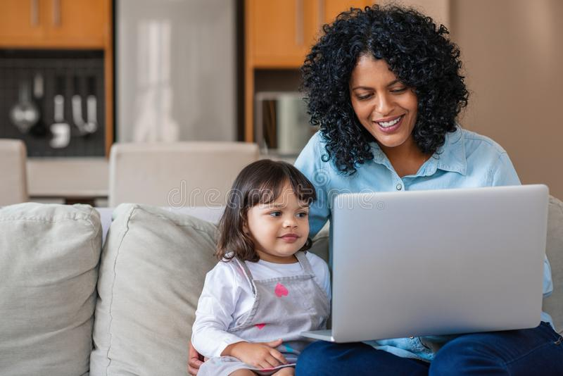 Smiling mother and little daughter watching something on a laptop royalty free stock image