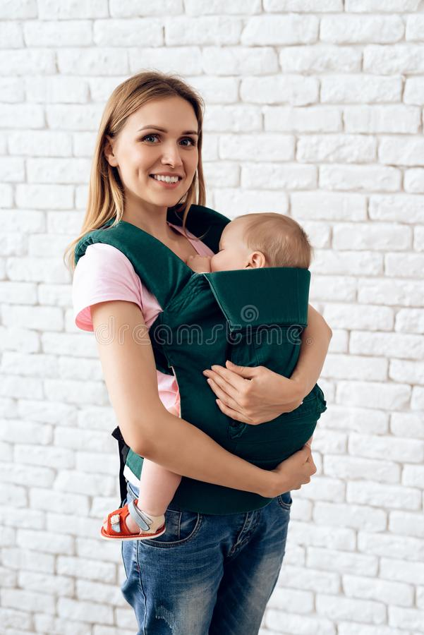 Smiling mother with newborn baby in baby sling. stock photo