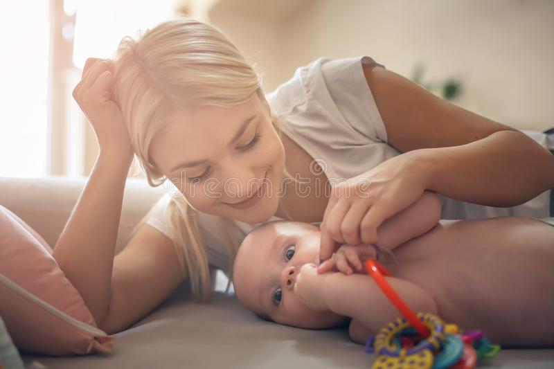 Smiling mother playing on bed with her baby boy at home. Close up stock image