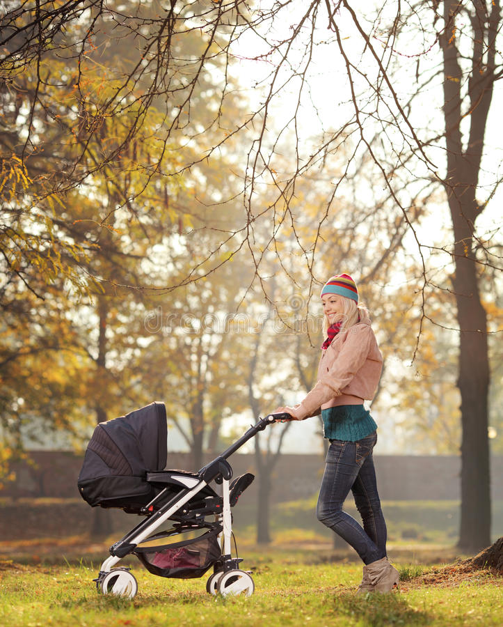 A smiling mother posing with a baby stroller in a park in autumn royalty free stock photos