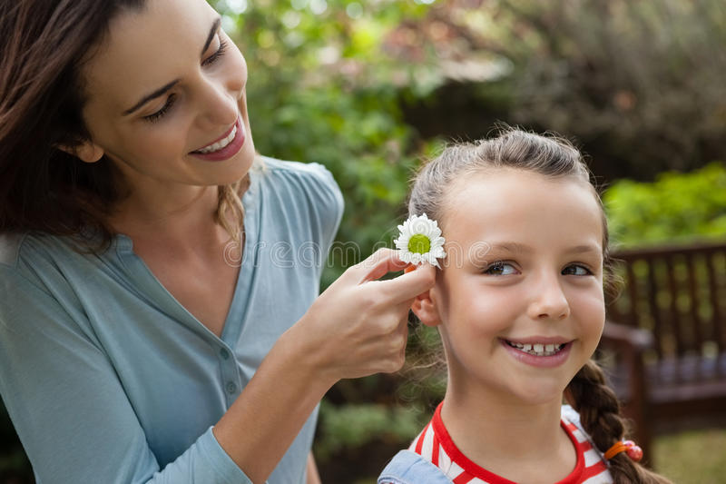 Smiling mother positioning white flower in hair of girl. At backyard royalty free stock photos