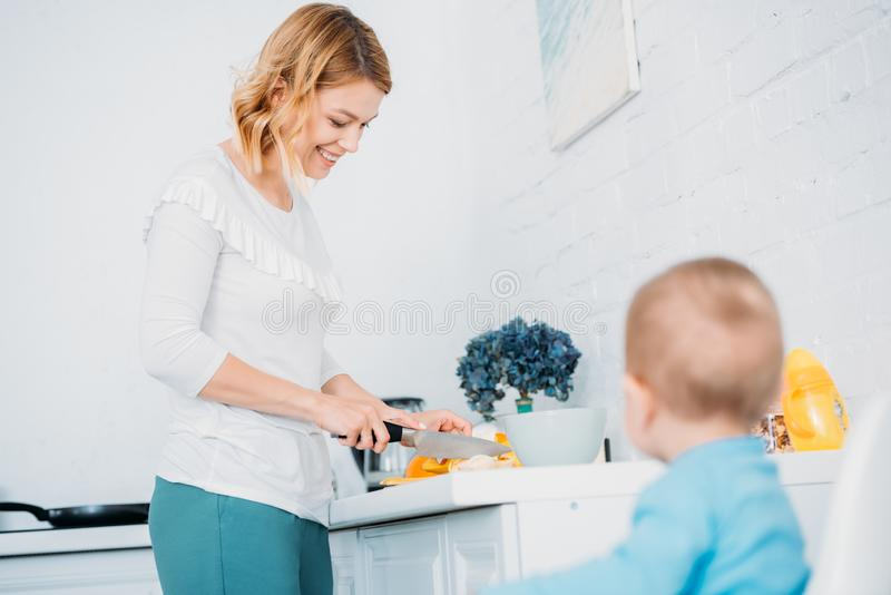 Smiling mother preparing dinner for her little child. While he sitting in feeding chair at kitchen stock images