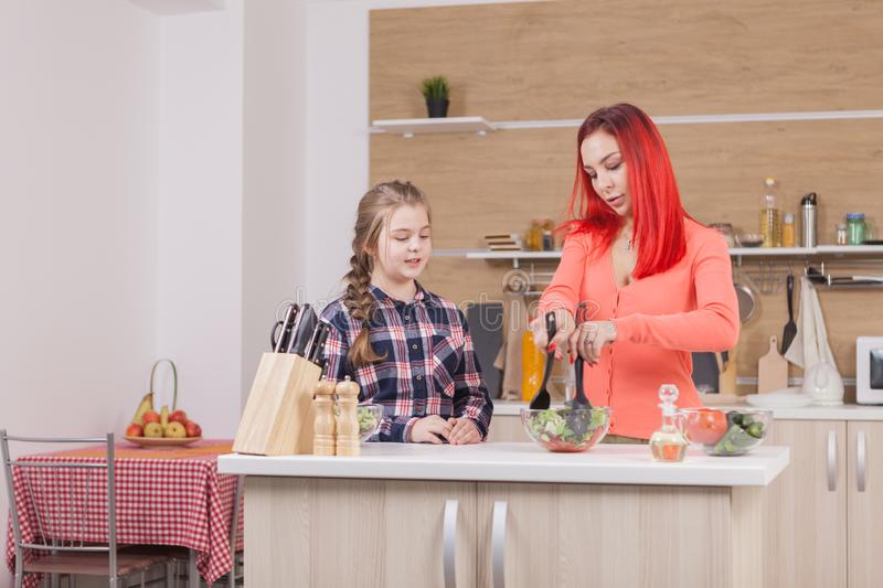 Smiling mother preparing salad with her daughter stock photography