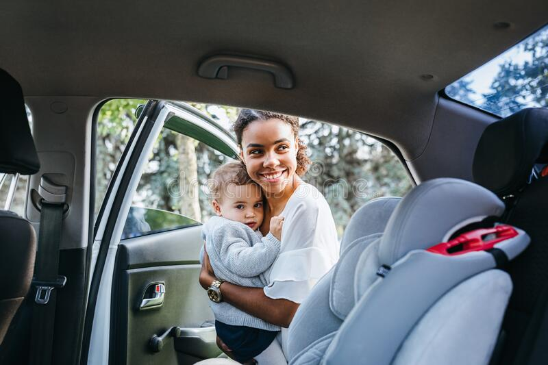 Smiling mother putting baby daughter in a car seat royalty free stock photo