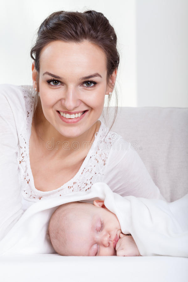 Smiling mother and sleeping baby. Smiling happy mother and sleeping baby stock image