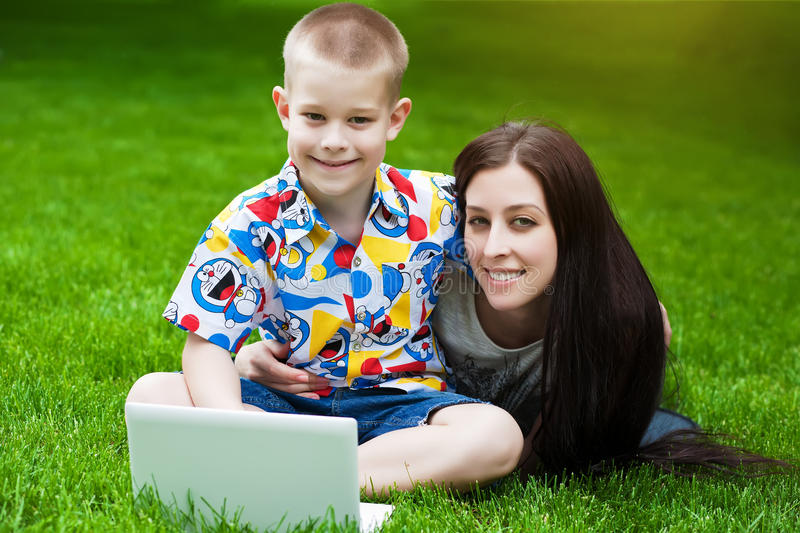 Smiling Mother and son laying on grass with laptop stock photos