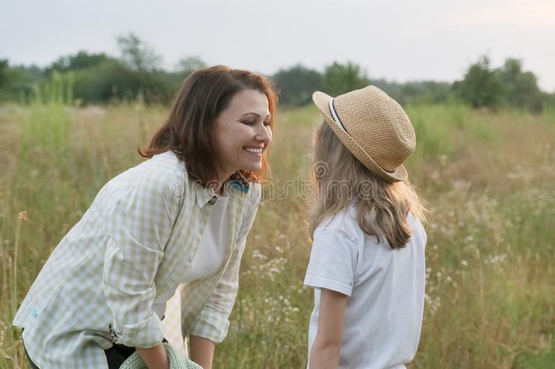 Smiling mother talking with child daughter, summer nature royalty free stock images