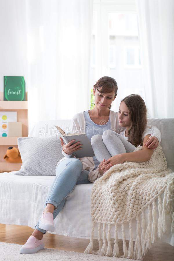 Smiling mother and teenager daughter sitting on the couch, reading book together royalty free stock images