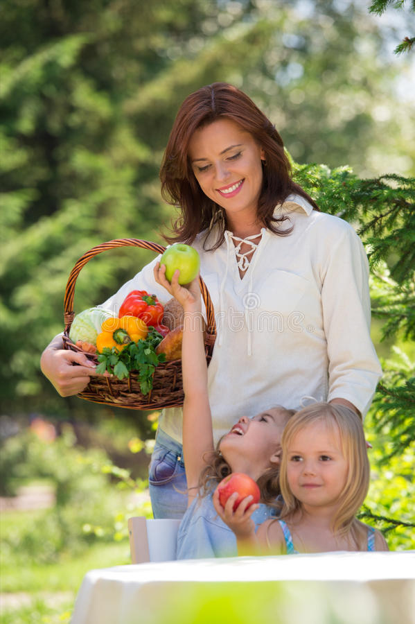 Smiling mother and two daughters having picnic royalty free stock images