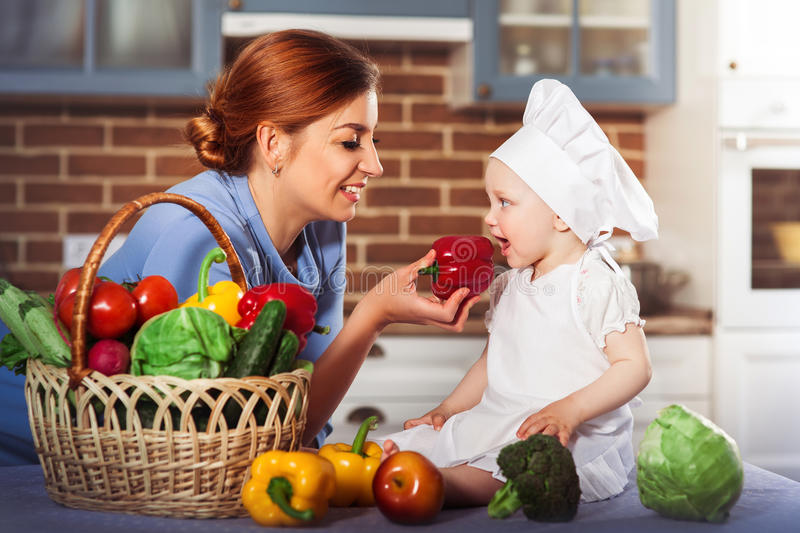Smiling mother wearing a blue dress feeds charming baby girl cook. royalty free stock images