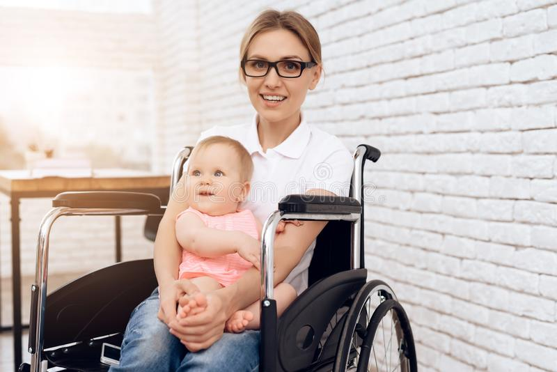 Smiling mother in wheelchair hugging newborn baby. stock photography