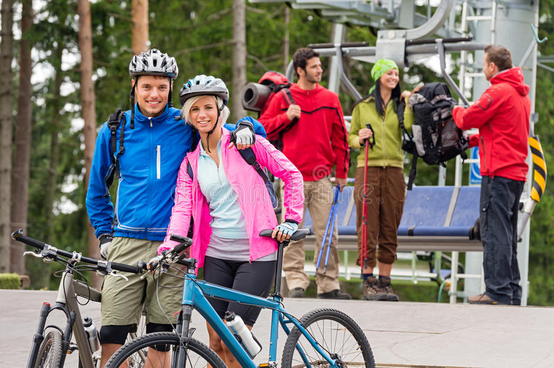 Mountain bikes couple and hikers after chair lift. Smiling mountain bikes couple and hikers waiting after chair lift trip stock photo