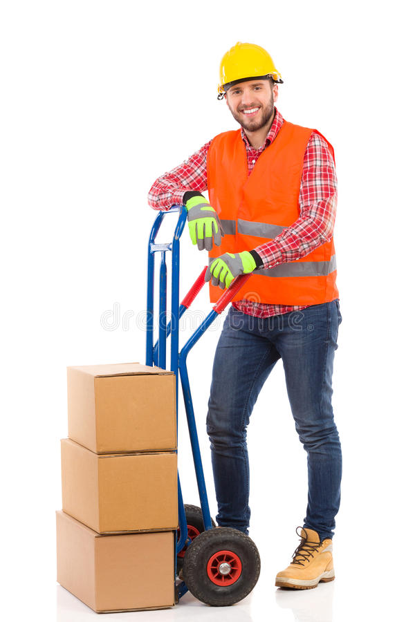 Smiling mover posing. Happy man in yellow hardhat and orange reflective vest posing with a delivery cart and looking at camera. Full length studio shot isolated stock photos