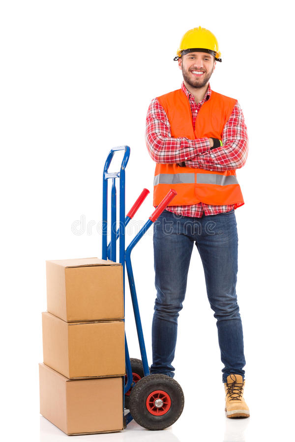 Smiling mover with a push cart. Smiling man in yellow hardhat and orange reflective vest posing with arms crossed next to delivery cart. Full length studio shot stock images