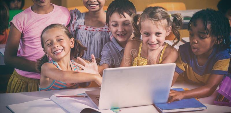 Smiling multi ethnic children using laptop stock photography