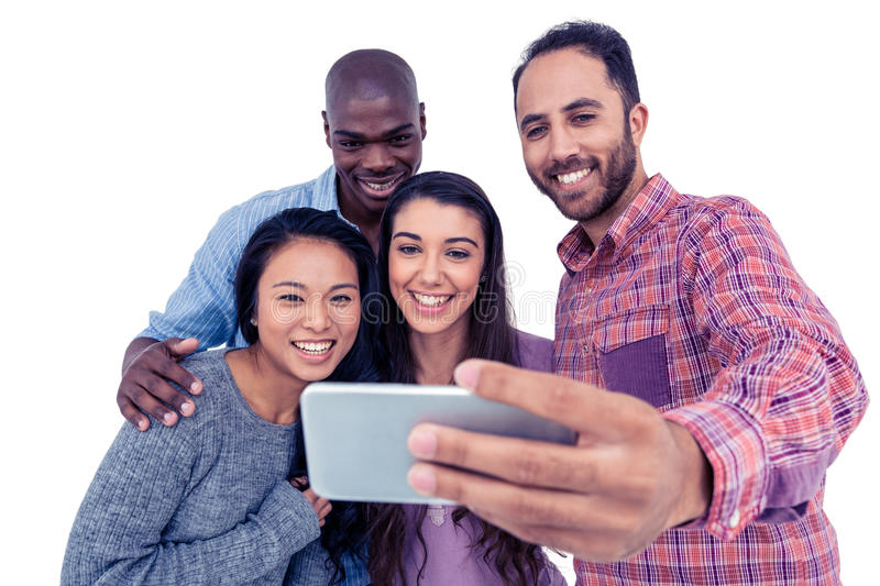 Smiling multi-ethnic friends taking selfie. While standing against white background stock photography