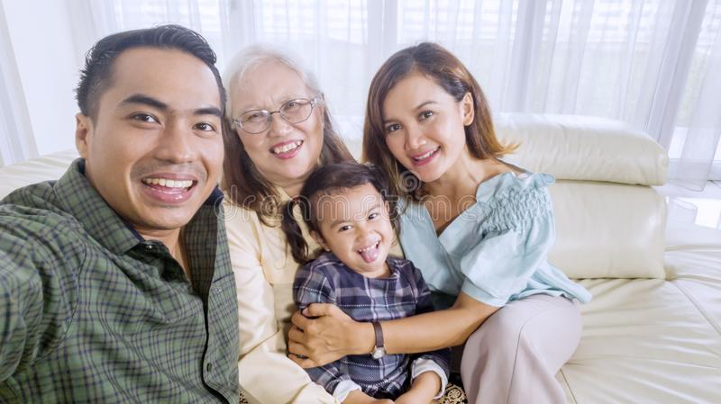 Smiling family takes a group picture at home royalty free stock photography