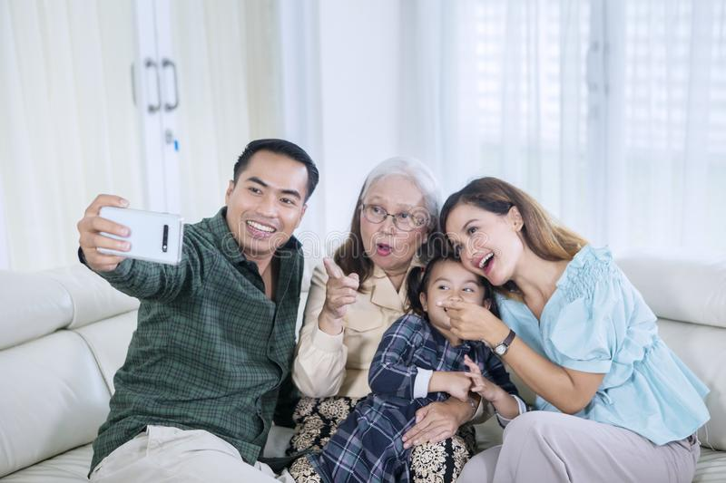 Smiling multi generation family takes selfie at home stock photography