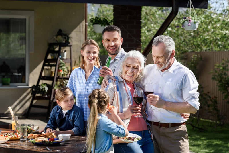 Smiling multi-generational family having picnic on patio at daytime stock photos
