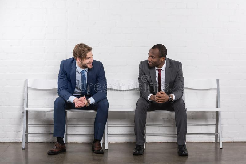 smiling multicultural businessmen looking at each other while waiting stock photography