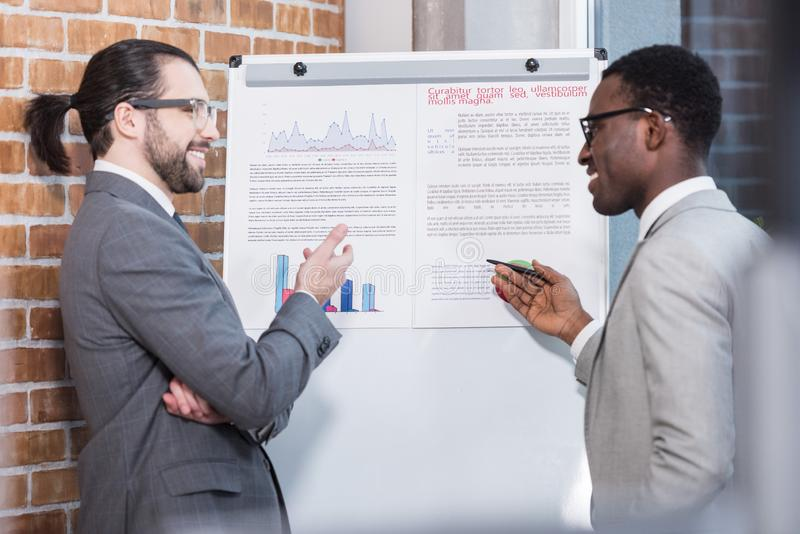 Smiling multicultural businessmen talking in front of white board with charts and graphs. In office stock photos