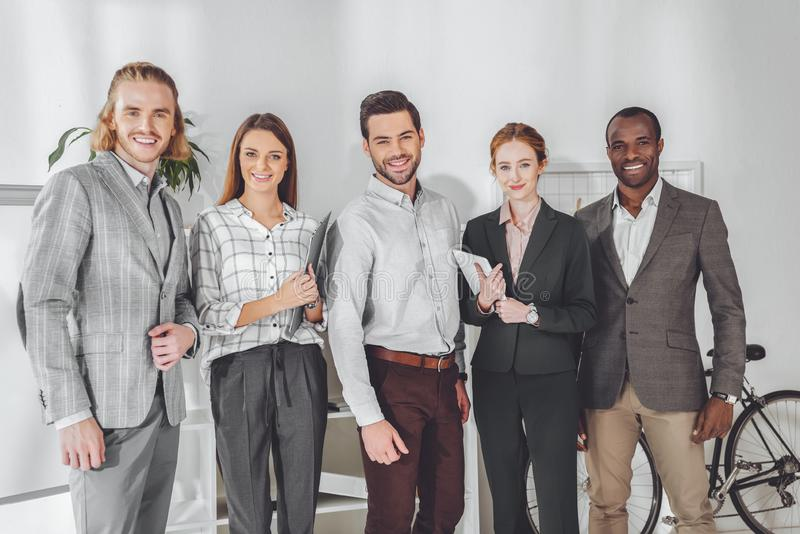 smiling multicultural businesspeople standing and looking stock photography