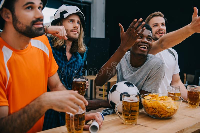 smiling multicultural group of male football fans gesturing by hands and watching soccer match stock image