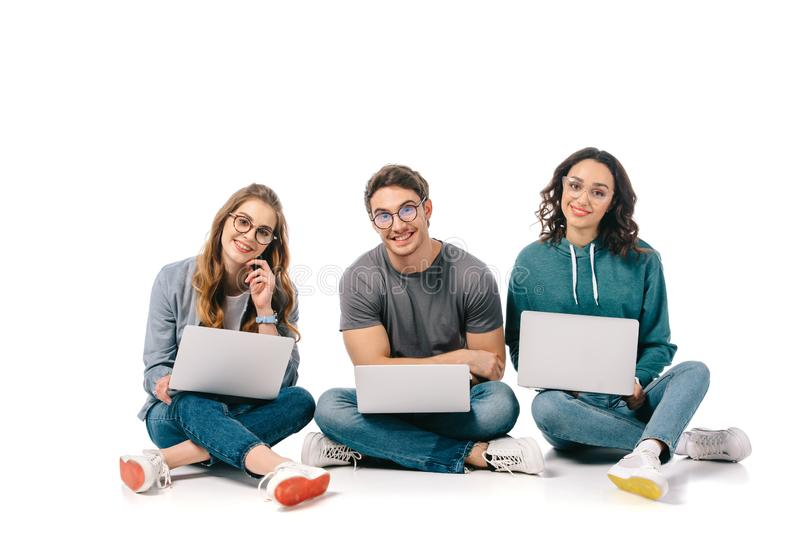 Smiling multicultural students sitting with laptops and looking at camera. On white stock photo