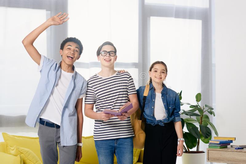 smiling multicultural teenagers greeting someone stock photos
