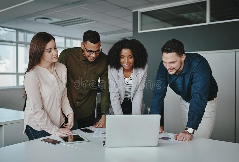 Smiling multiethnic coworkers working together in office watching online project application on laptop over the office royalty free stock image