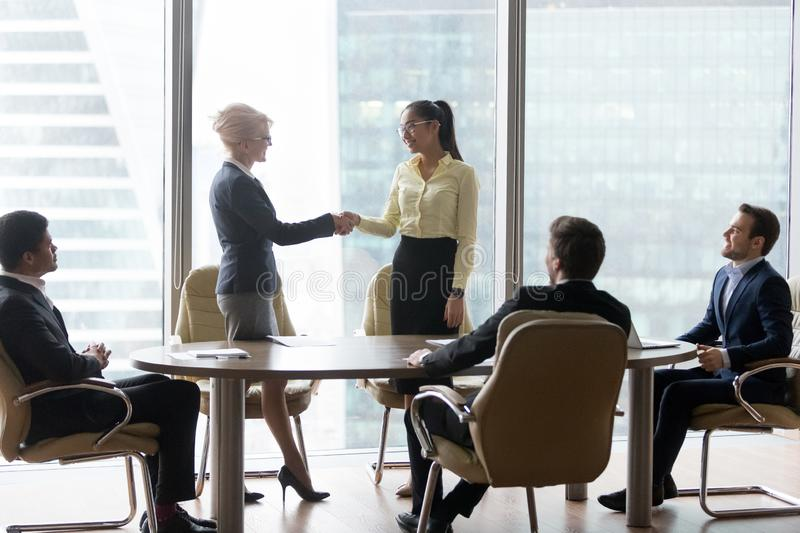 Smiling multiracial business people at meeting shaking hands royalty free stock photo