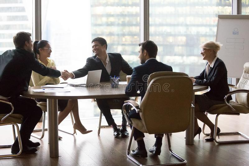 Smiling multiracial business people sitting at meeting stock image
