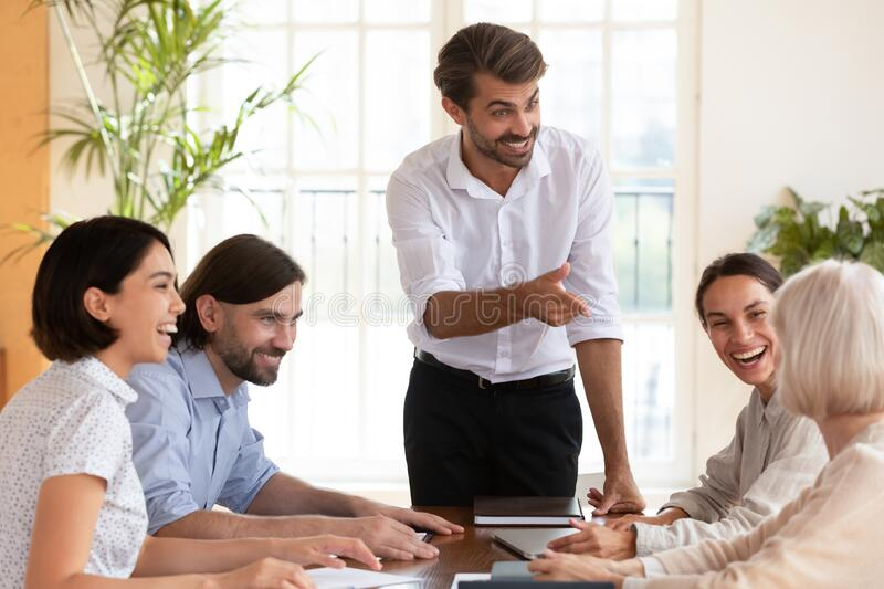 Smiling multiracial colleagues brainstorm at office meeting stock photography
