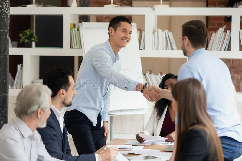 Smiling male employees handshake greeting at meeting. Smiling multiracial colleagues handshake greeting at business meeting in office, happy male employees shake royalty free stock image
