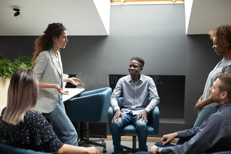 Smiling multiracial colleagues listening to skilled female team leader. royalty free stock photos