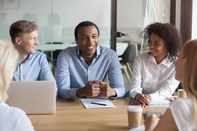 Smiling multiracial colleagues negotiate cooperating at meeting. Smiling multiethnic colleagues brainstorm at office desk discussing financial statistics at stock images
