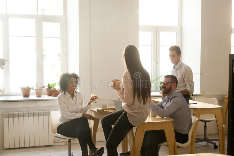 Smiling multiracial colleagues talking while eating pizza at off royalty free stock photography