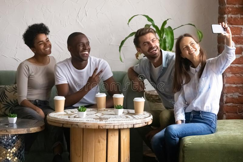 Smiling multiracial friends posing for selfie in cafe royalty free stock photography