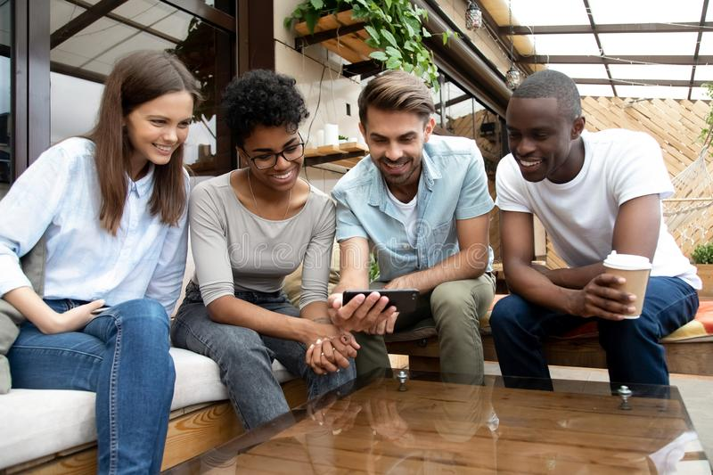 Smiling multiracial people relax watching video on cellphone stock image