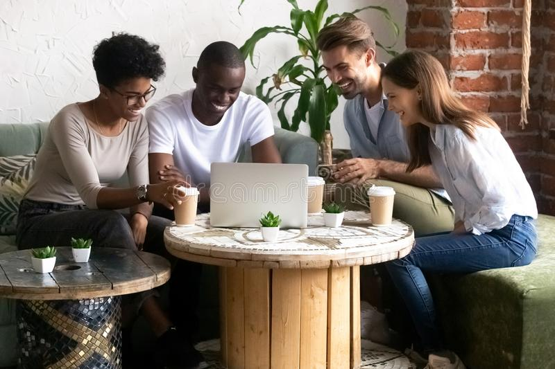 Happy diverse friends have fun watching funny video in caf stock images