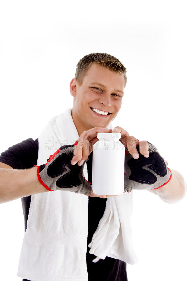 Smiling muscular guy showing medicine bottle royalty free stock photography