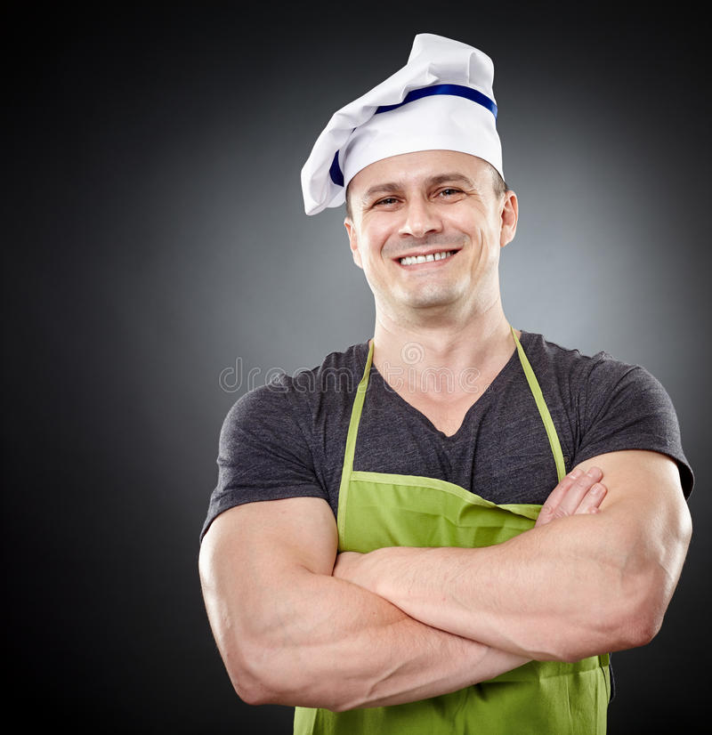 Smiling muscular man cook with arms folded. Studio shot of a muscular man cook with arms folded over gray background stock images