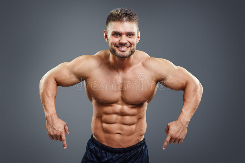 Smiling muscular man pointing down. Half body studio shot isolated on grey royalty free stock photos